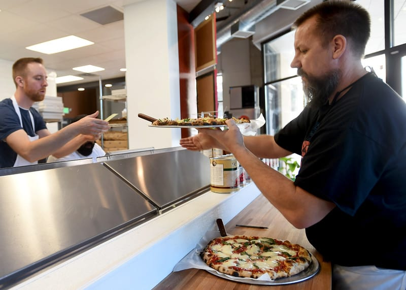 """John Neau, left, hands owner Steve Lott a pizza to serve to customers at Big River Pizza in St. Paul on Thursday, July 30, 2015. (Pioneer Press: Holly Peterson)"""